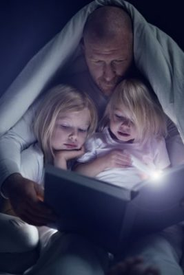 Father and daughters reading a book at bedtime